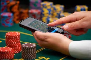 Finger som dras över skärm på en smartphone över ett roulettebord med spelmarker