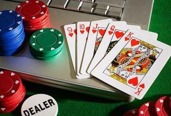Spelmarker och spelkort med nio, tio, knekt, dam och kung i hjärter ovanpå en öppen bärbar dator